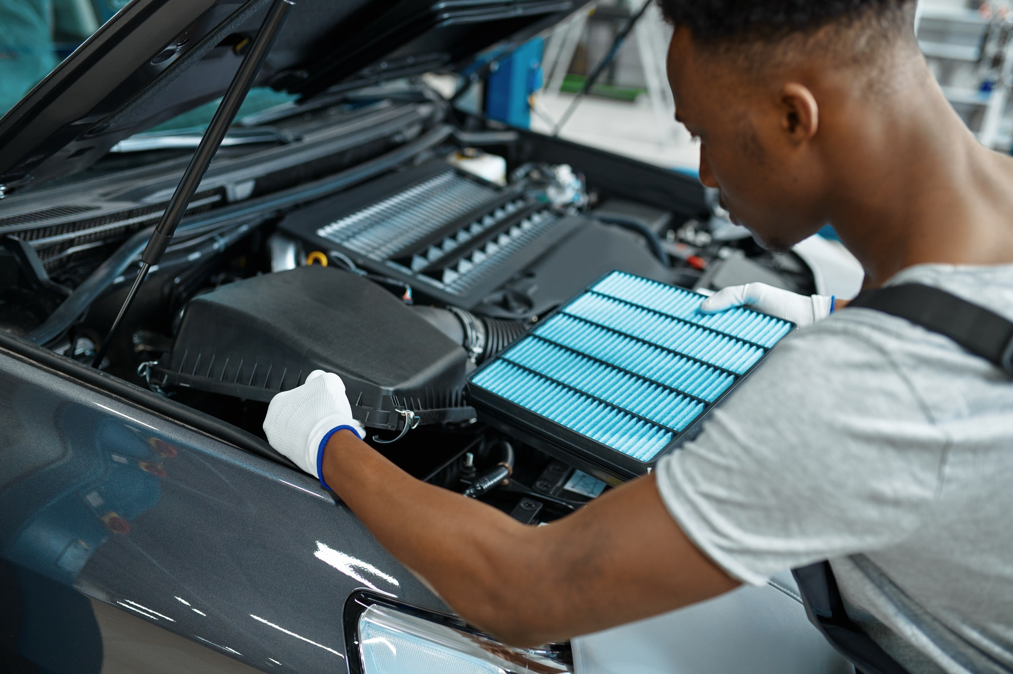 Male mechanic changes air filter, car service