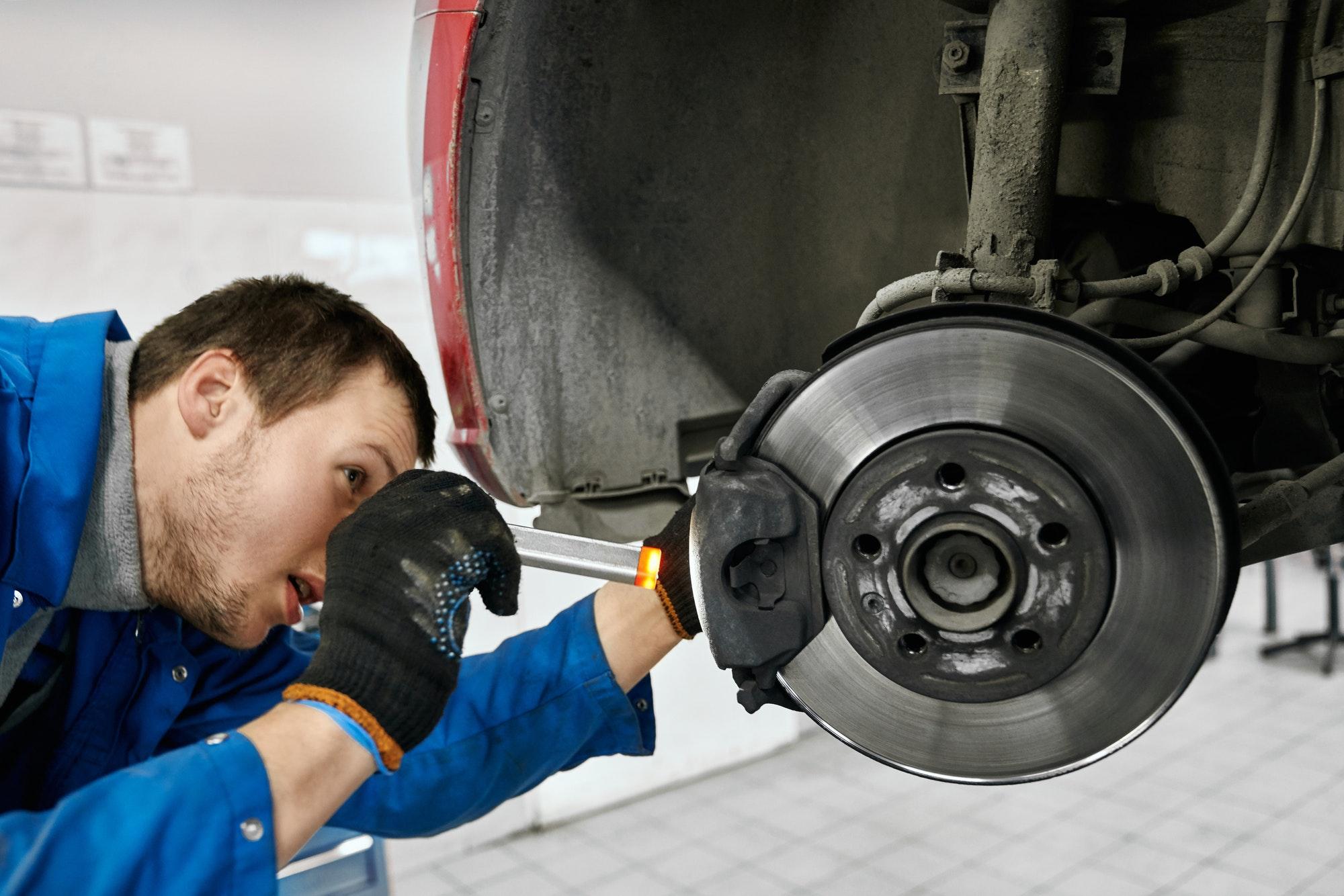 Male mechanic holding flashlight and examining brake pads