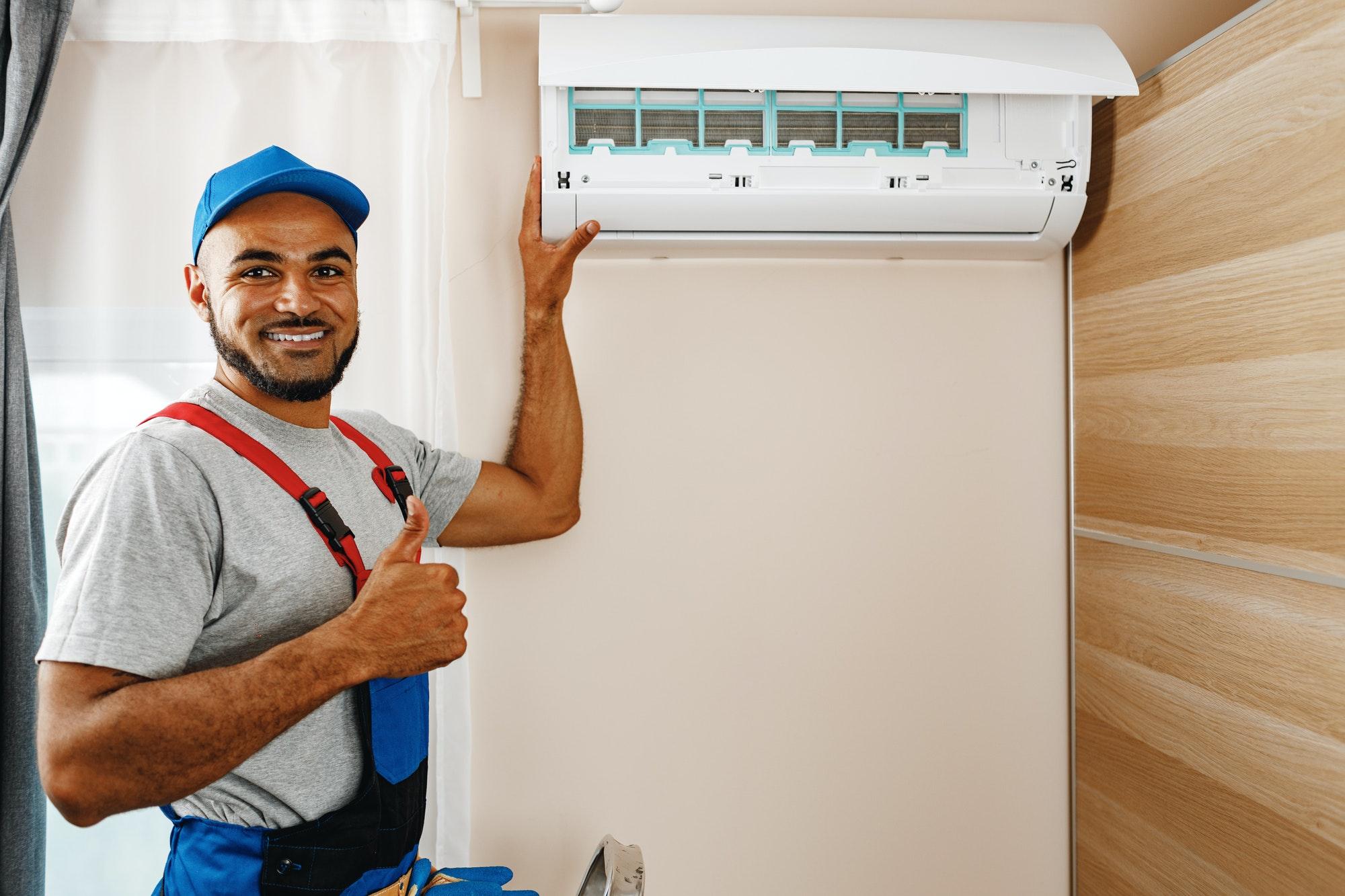 Professional repairman installing air conditioner in a room