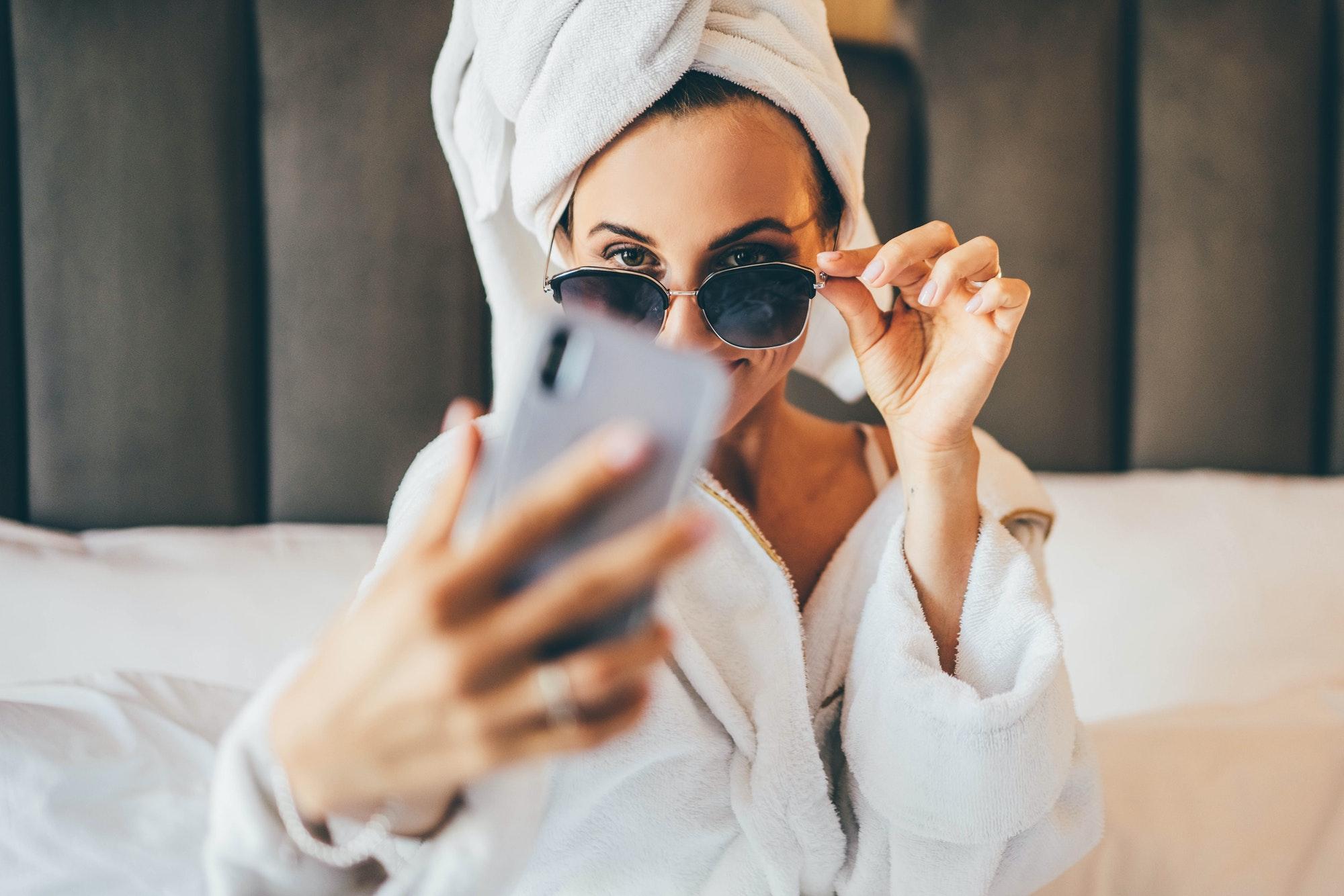 woman in towel and bathrobe sitting, making selfie and having fun