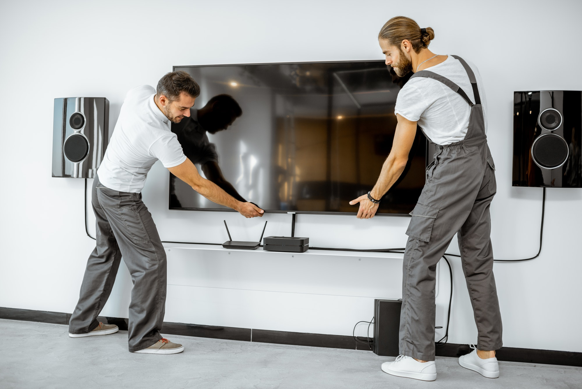 Workmen installing television at home
