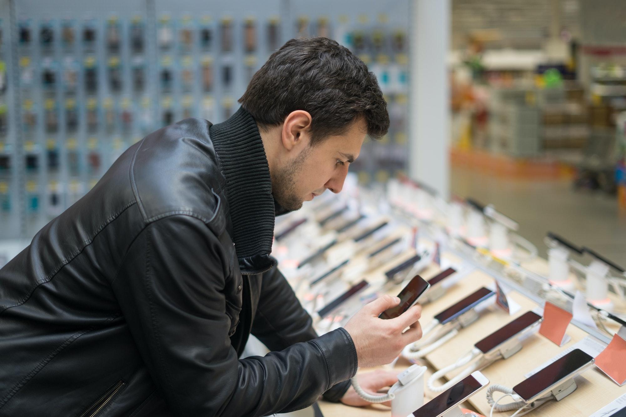 young male customer choosing smartphone