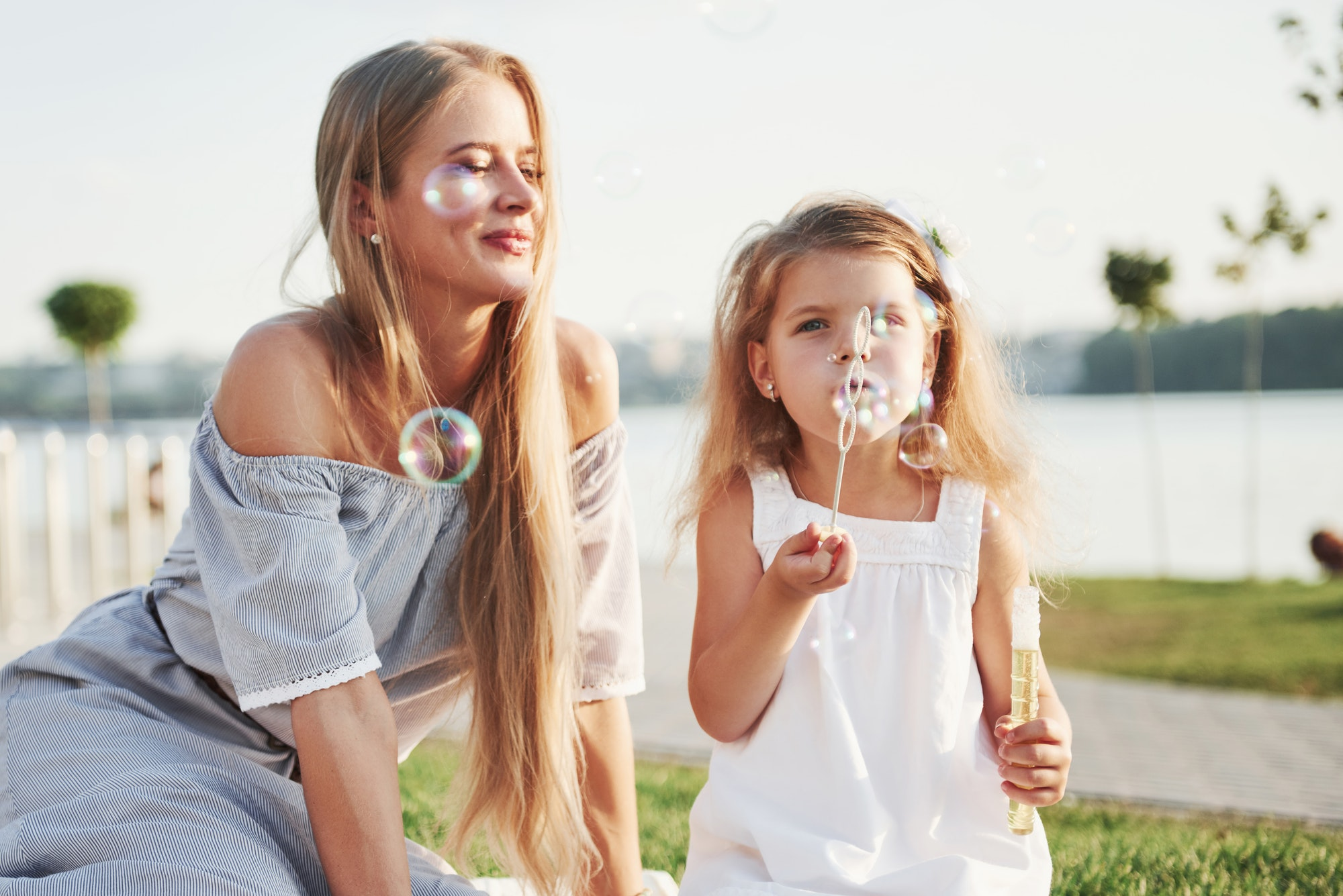 A wonderful girl child makes bubbles with her mom in the park