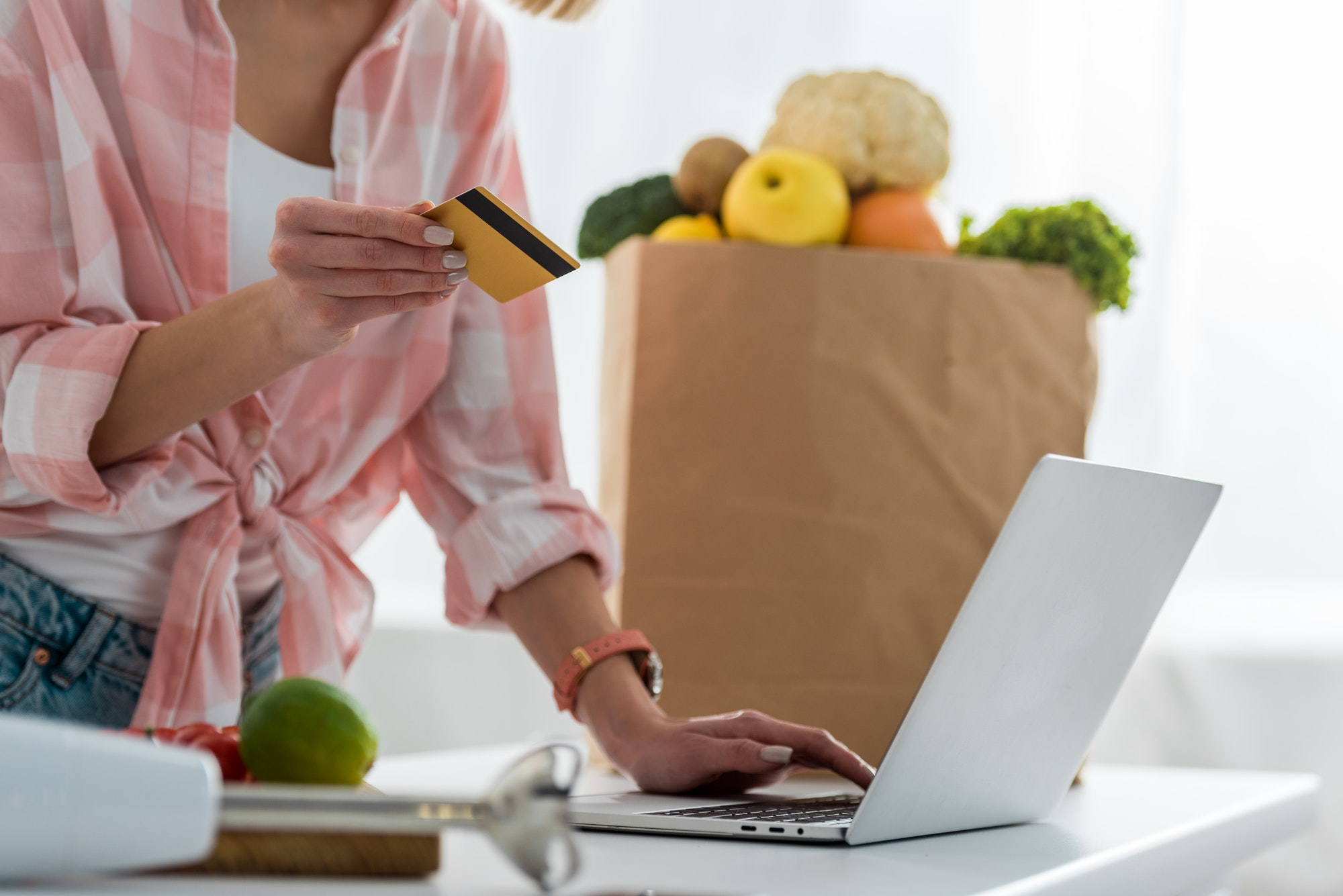 cropped view of young woman holding credit card while using laptop near paper bag with groceries