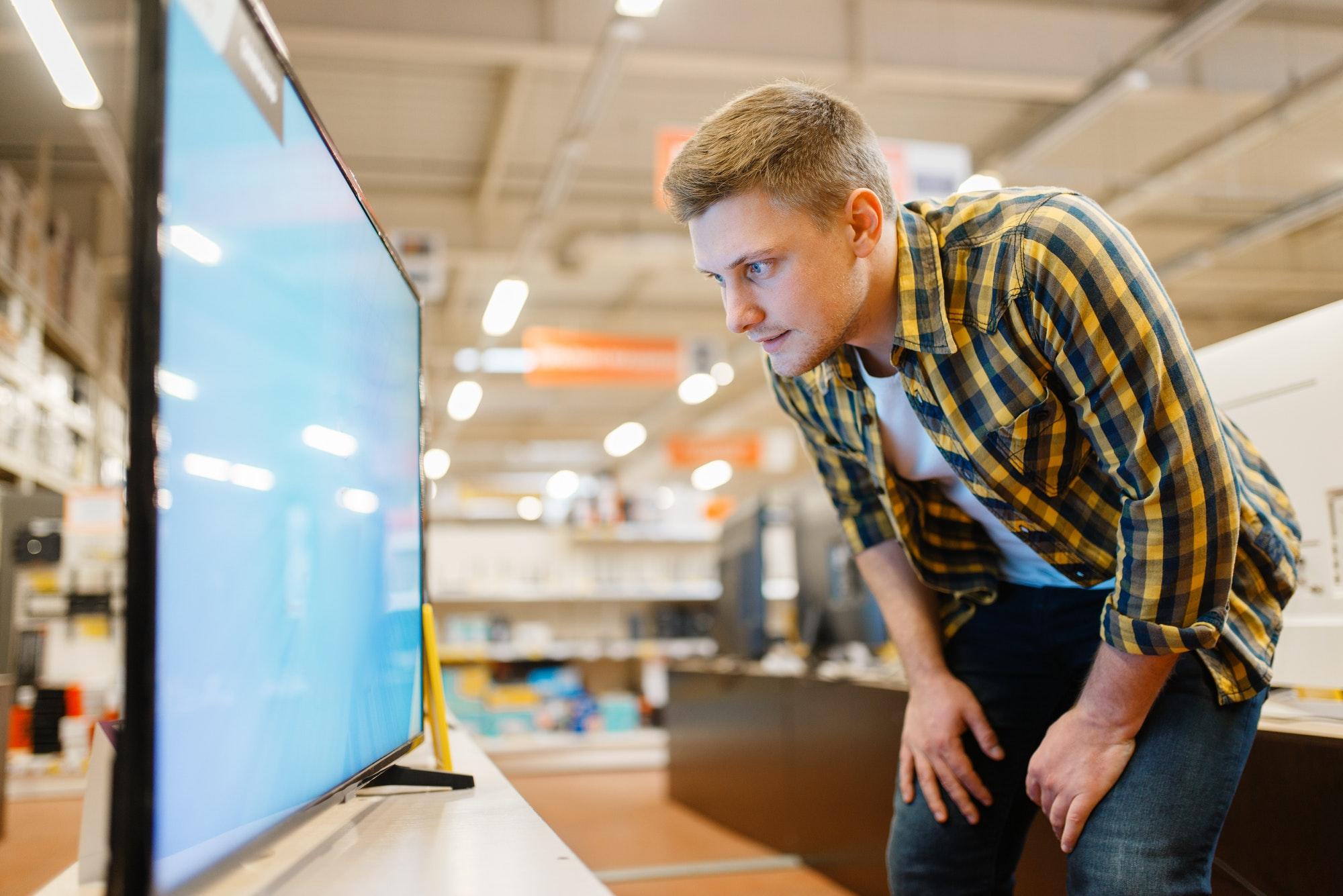 Man choosing TV in electronics store