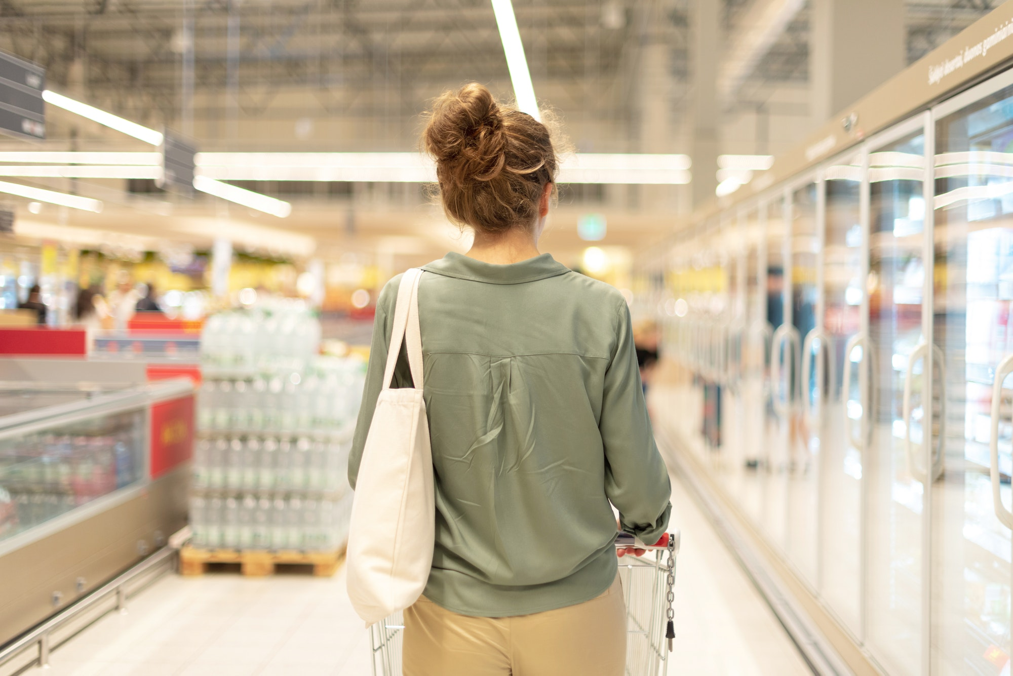 Young woman with shopping card and cotton shopper bag is shopping in supermarket. Copy space