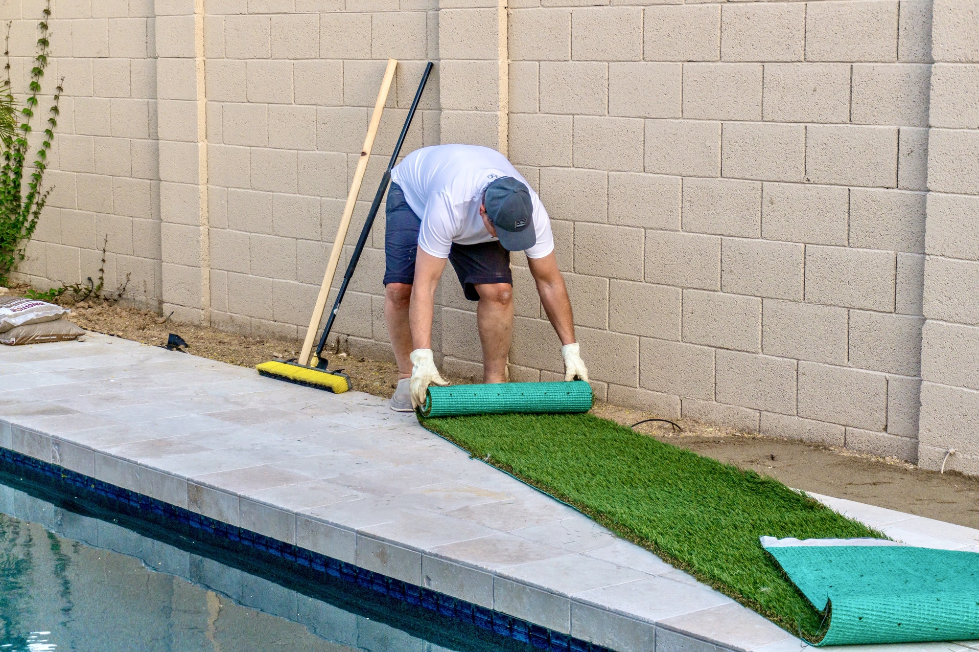 Adult male rolling out and installing artificial turf in a small space