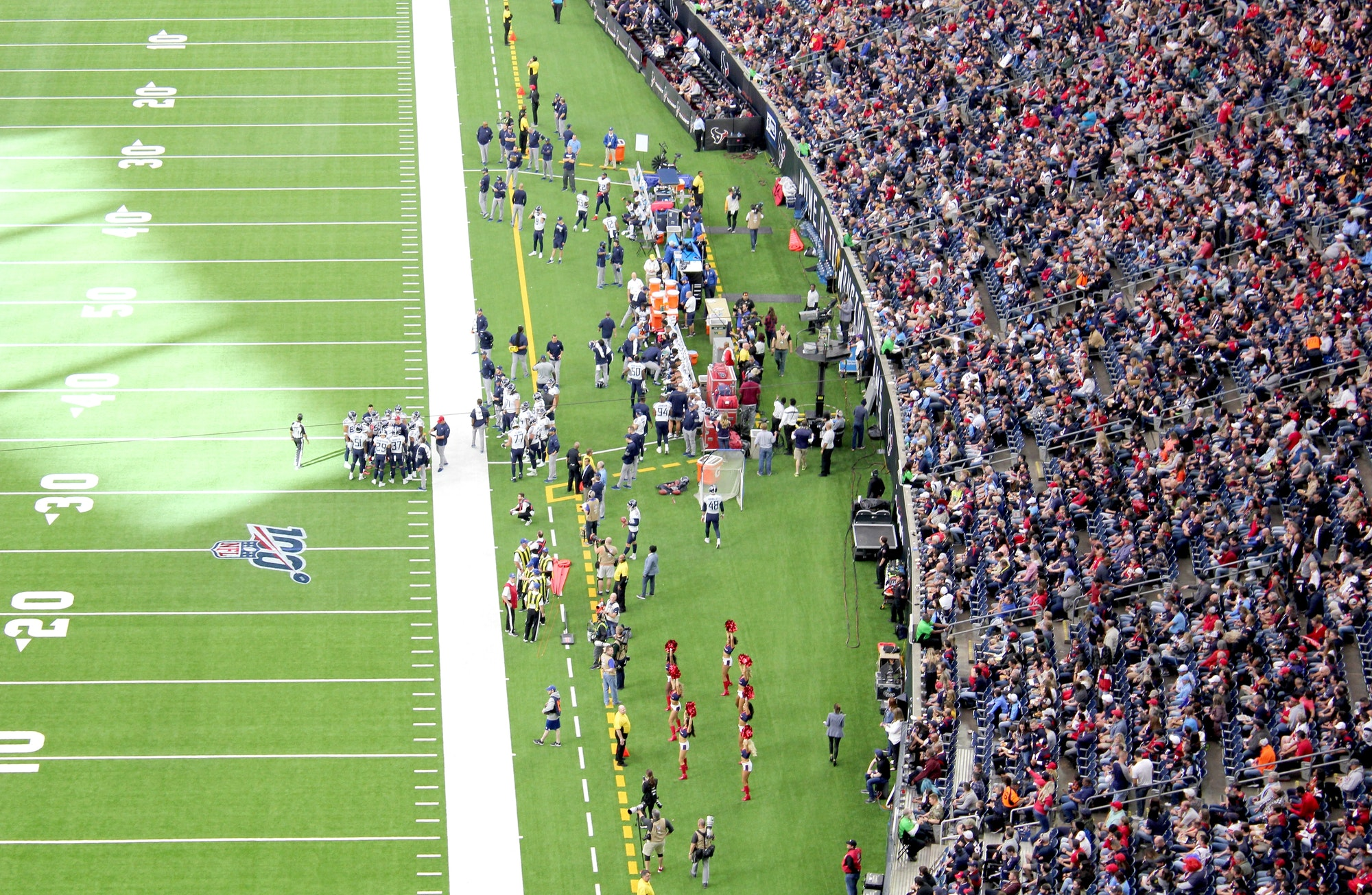 An audience of sports fans watching an NFL football game in a stadium